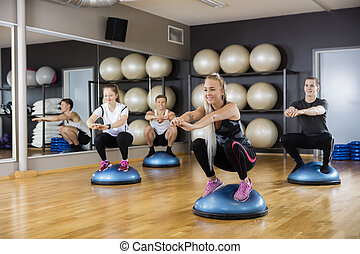 Friends Doing Squatting Exercise On Bosu Ball In Gym - Male...