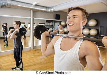 Man Lifting Barbell With Friends In Fitness Studio - Smiling...