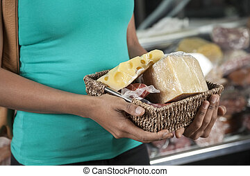 Woman Holding Cheese And Meat Basket In Grocery Store