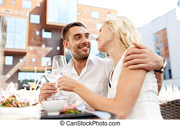 happy couple drinking wine at open-air restaurant - love,...