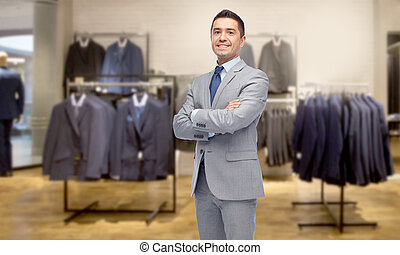 happy businessman in suit over clothing store - business,...