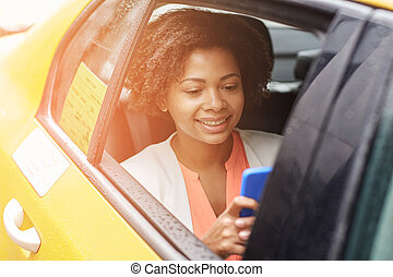 happy african woman texing on smartphone in taxi - business...