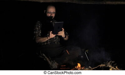 Man near campfire making photo on tablet