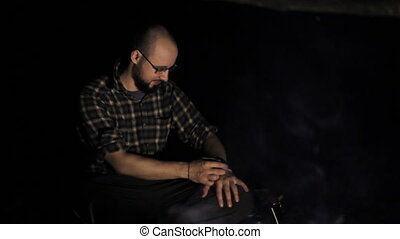 Man near campfire touch smartwatch at night