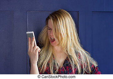 Portrait angry young woman screaming on mobile phone...