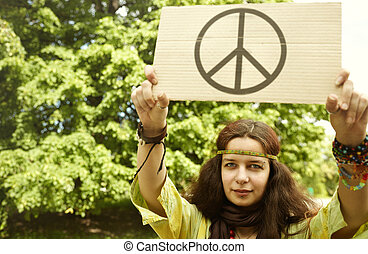 Hippie - real young woman with cardboard with well-known...