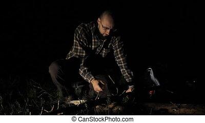 Man cuts a small tree at night - White man cuts a small tree...