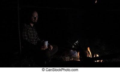 Man drinking tea near campfire at night