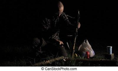 Man cuts a small tree at night