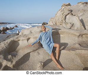 beauty young woman among rocks at sea dreaming relaxing,...
