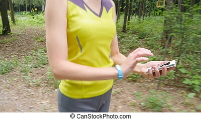 Woman running with fitness tracker in forest