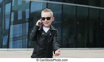 baby boy 7 - 8 years in sunglasses with phone