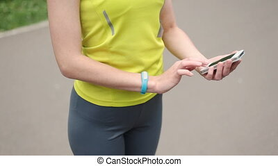 Womens hands with a sports bracelet and smart phone close-up...