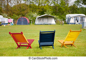 Campground with colorful empty chairs to sit down