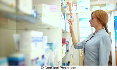 female pharmacist standing at counter in pharmacy - Portrait...
