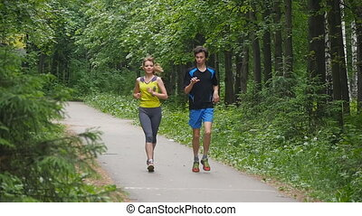 Happy couple jogging in the park, slow motion - Happy couple...