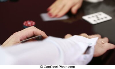 dealer handling playing cards at a poker table. Black...