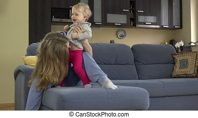 Beautiful woman tickle toddle child stomach sitting on sofa...