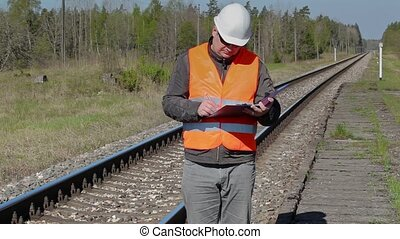 Railroad worker writing near railway