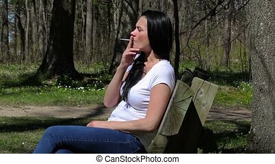 Woman smoking in the park on the
