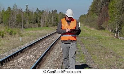 Railroad worker walking and writing near railway