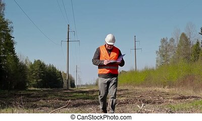 Electrician writing near the high-voltage power line
