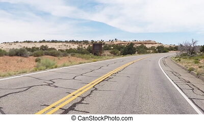 Canyonlands 7: Driving uphill and around a bend through the...