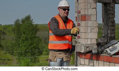 Builder with spirit level near to