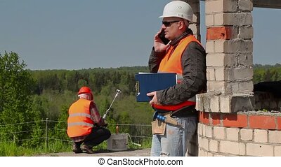 Builder using smart phone near to the building