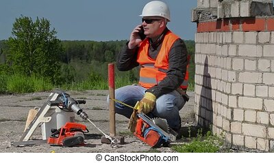 Builder talking on smart phone near to the unfinished...