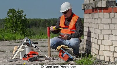 Builder using tablet PC and measuring tape
