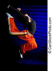 Dancer jumping on dark background
