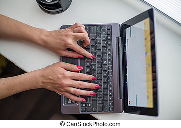 Female hands working on ultrabook on the windowsill