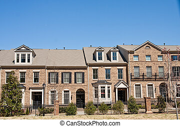 Brown Brick Townhouses Under Blue Sky - A row of brown brick...