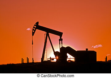 Pumpjack in Red Sunset - an oil pumpjack silhouetted in the...