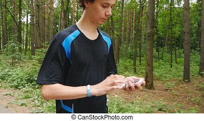 young man using fitness bracelet during morning run in...