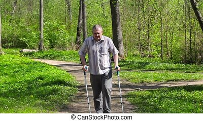 Tired disabled man with crutches walking in the park