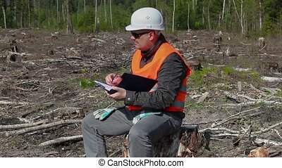 Lumberjack writing and thinking in forest