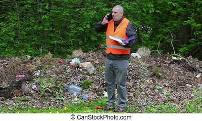 Environmental officer talking on smart phone in polluted...