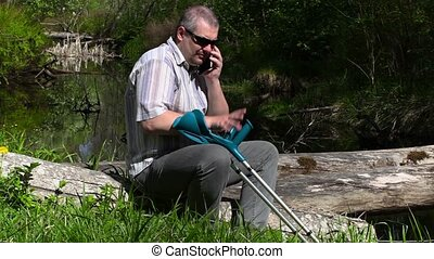 Disabled man with crutches talking on smart phone near river