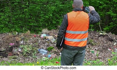 Environmental officer take pictures on smart phone in...
