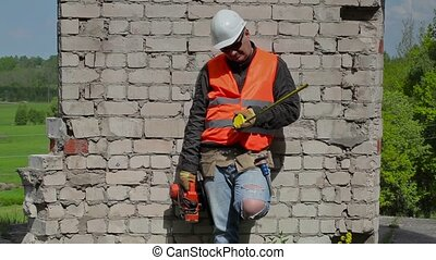 Thoughtful builder with the measuring tape near to the wall