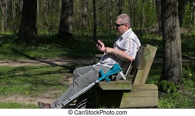 Disabled man talking on smart phone on bench in the park