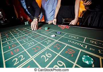 Hand put a bet on the roulette table, casino, people