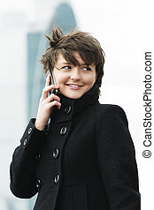 Woman on cellphone in windy day - Smiling young pretty woman...