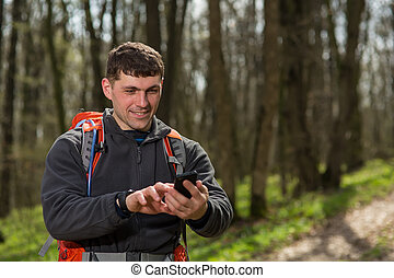 Man hiker taking photo with smart phone in forest - Man...