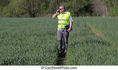Farmer with smartphone walking on the green cereal field