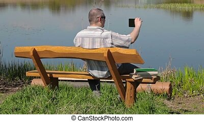 Man take pictures on smartphone on the bench near river