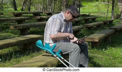 Disabled man with crutches on bench in the park and using...