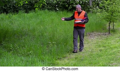 Landscaping manager writing near the bad quality cutting...